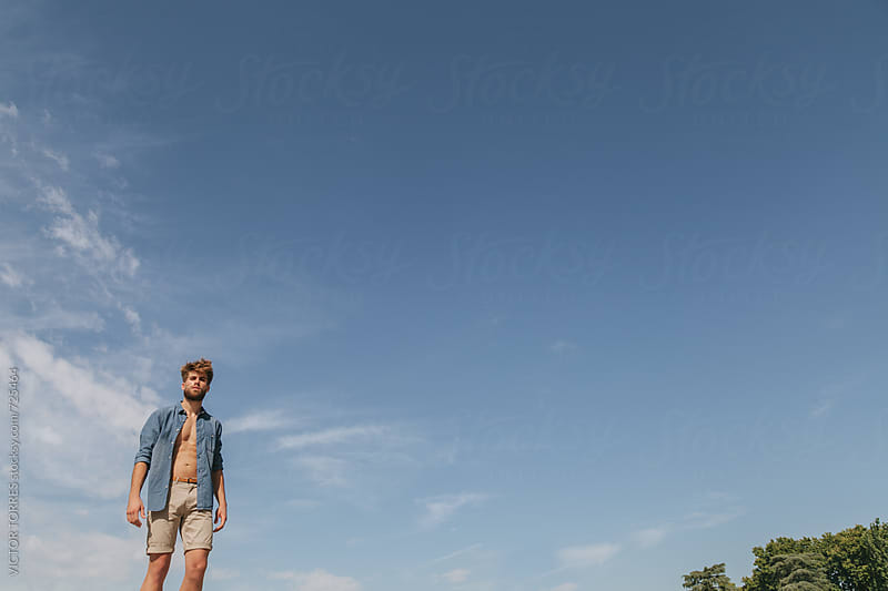 Young Man with Summer Outfit Against a Radiant Blue Sky by Victor Torres for Stocksy United