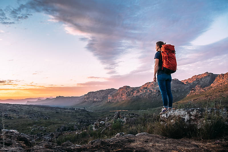 Female hiker with backpack in a mountainous valley enjoying a sunset view by Micky Wiswedel for Stocksy United