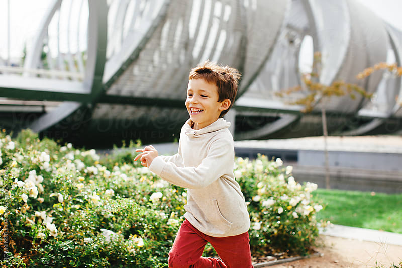 Smiling little boy running in the park. by BONNINSTUDIO for Stocksy United