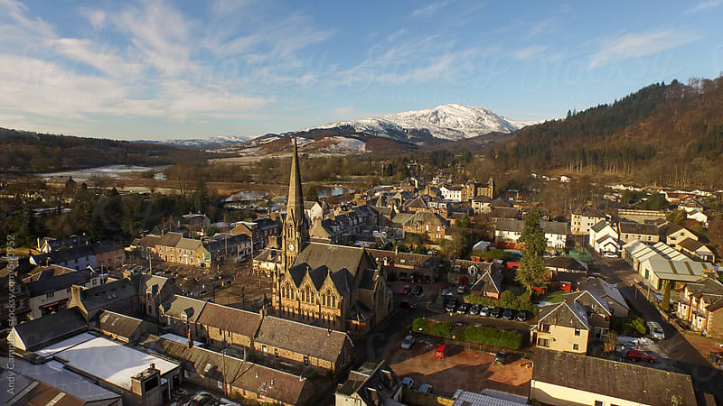 An aerial view of a Scottish village looking toward the Scottish Highlands. by Andy Campbell for Stocksy United