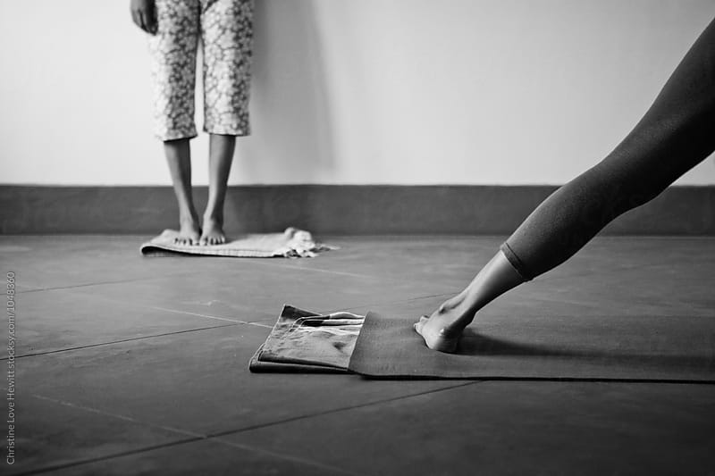 Feet of yoga teacher and student  by Christine Hewitt for Stocksy United