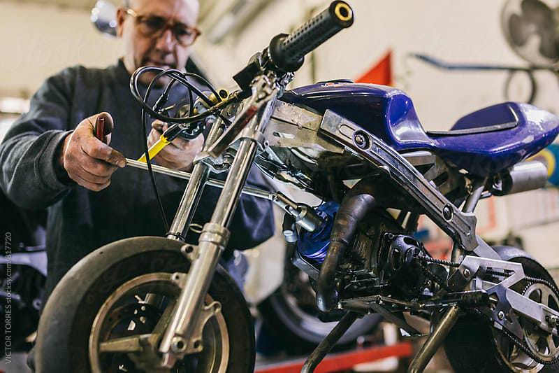 Mechanical Operator in a Motorbike Workshop by Victor Torres for Stocksy United