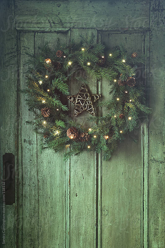 Holiday wreath on old wooden door by Sandra Cunningham for Stocksy United