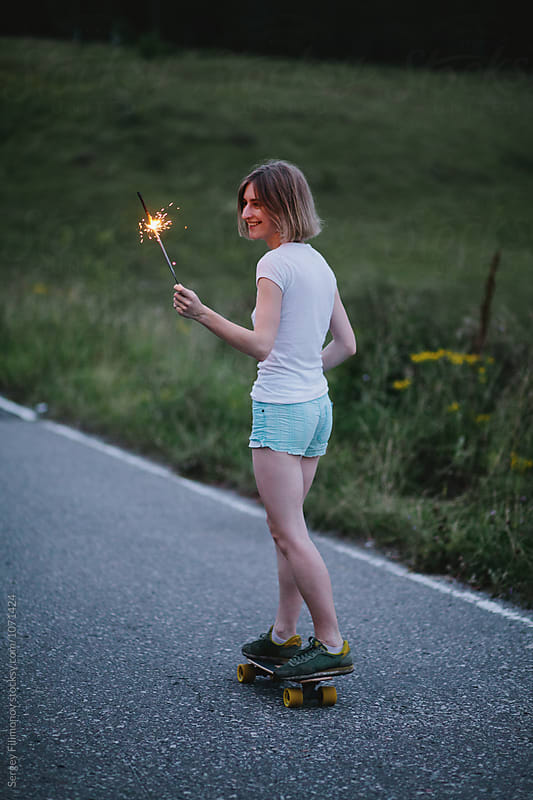 beautiful young blond woman riding a longboard with a burning sparkler by Sergey Filimonov for Stocksy United