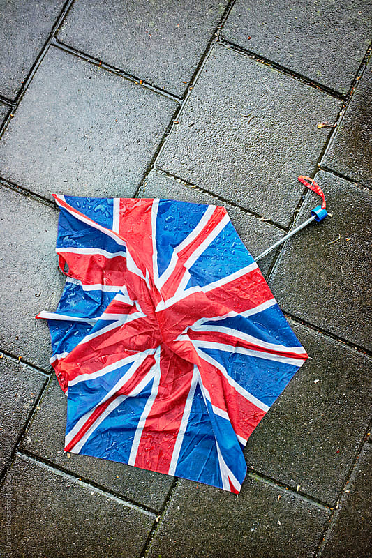 A broken umbrella  on the pavement by James Ross for Stocksy United