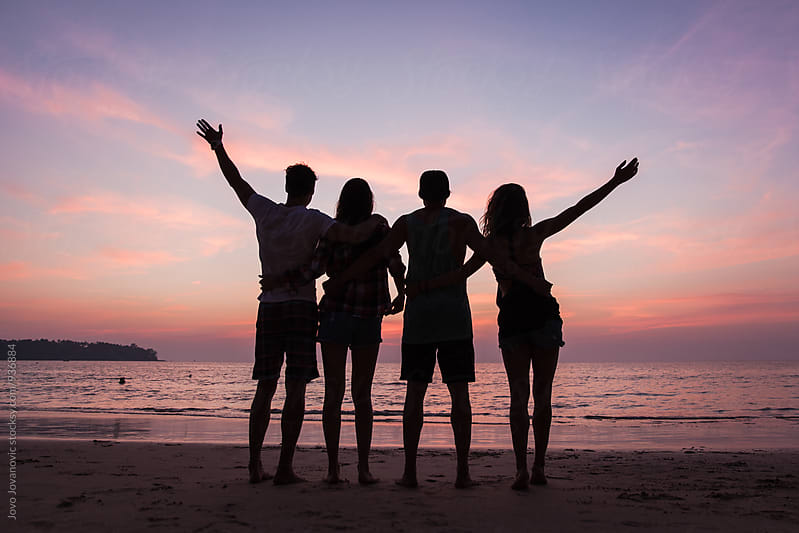 Four friends watching a sunset together by Jovo Jovanovic for Stocksy United
