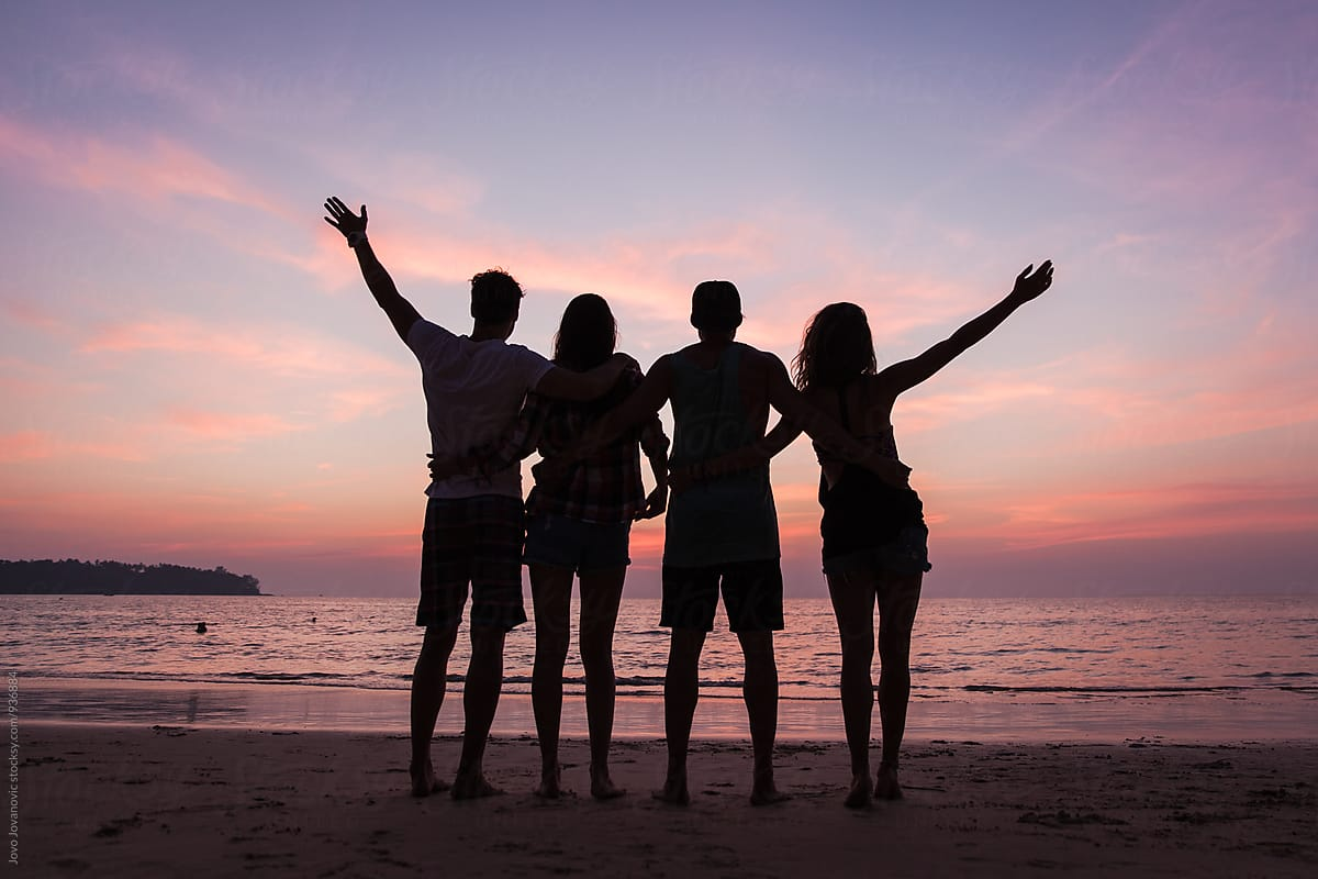 Four friends watching a sunset together by Jovo Jovanovic - Stocksy United