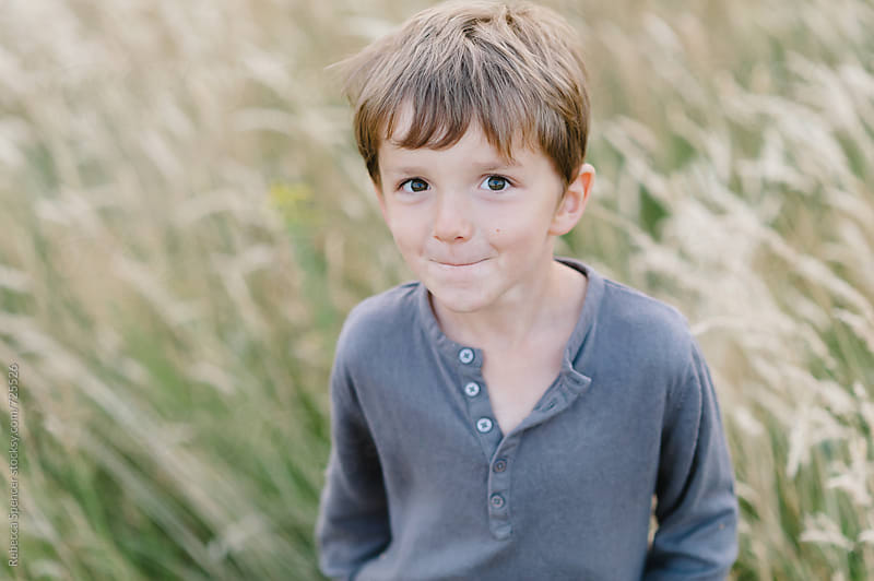 Cute child in corn field looks at camera by Rebecca Spencer for Stocksy United