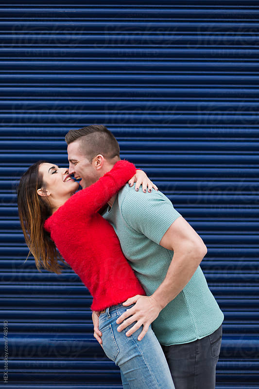 Young Couple Together Against a Blue Shutter by Mattia Pelizzari for Stocksy United