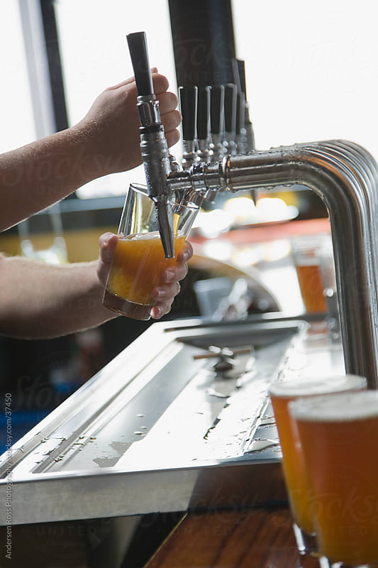 Close-up of bartender's hands pouring beer in bar by Andersen Ross Photography for Stocksy United