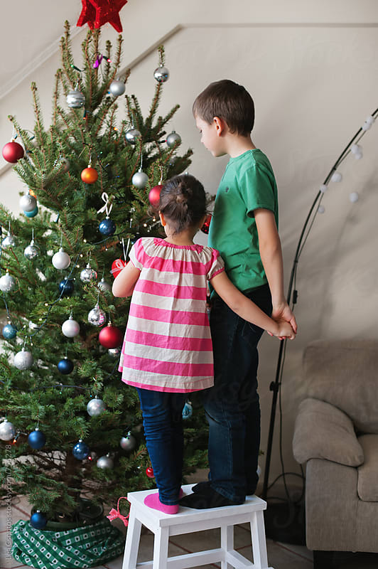Brother and sister standing on a stool decorating a christmas tree by Lea Csontos for Stocksy United