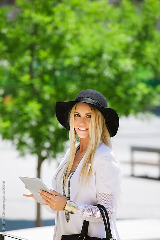 Young businesswoman walking on the street with digital tablet. by BONNINSTUDIO for Stocksy United