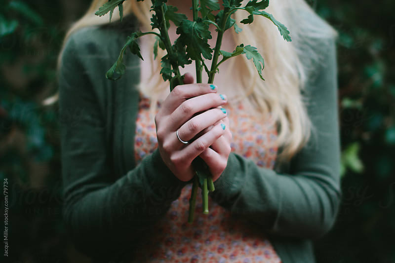Girl holding flower stems by Jacqui Miller for Stocksy United