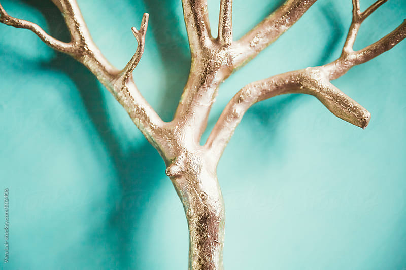 Golden branch on blue background by Vera Lair for Stocksy United