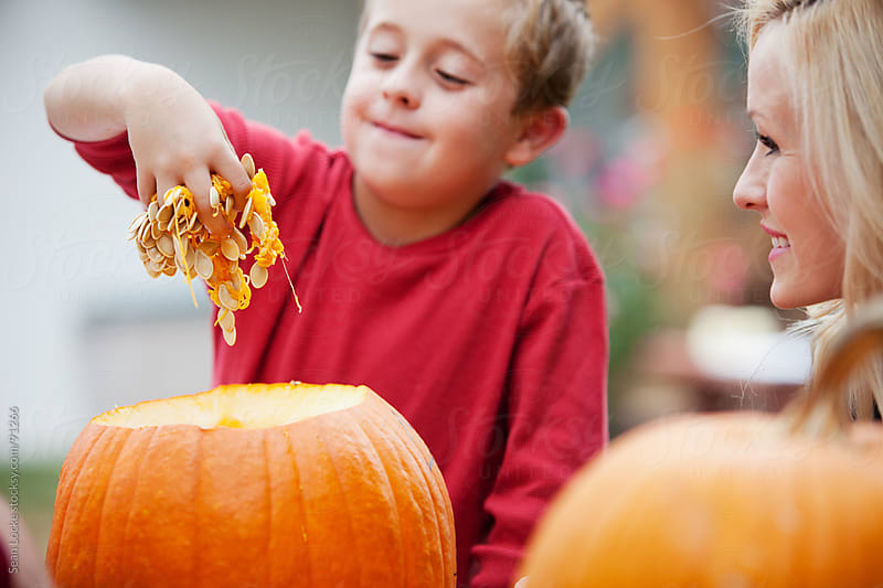 Pumpkins: Boy Pulls Guts Out Of Pumpkin by Sean Locke for Stocksy United