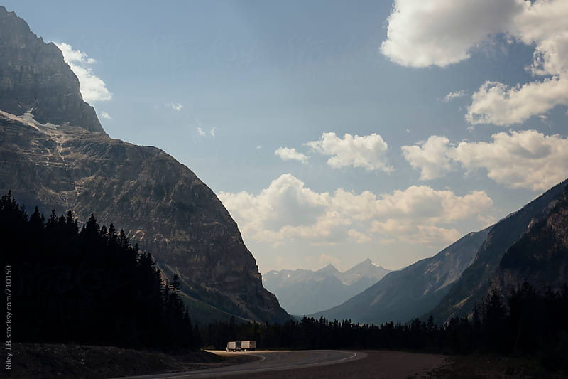 Two transport trucks drive on highway through mountains by Riley Joseph for Stocksy United