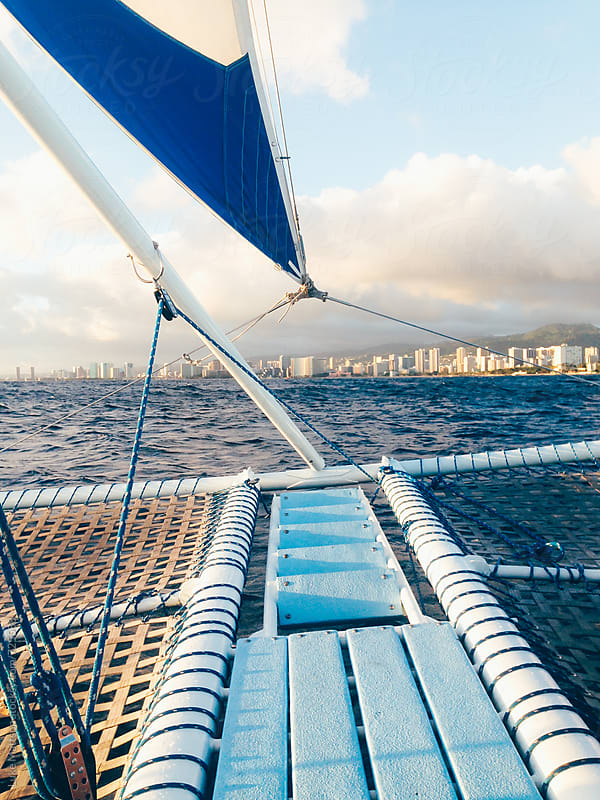 The Bow And Foremast Of A Catamaran Sailing Off The Coast Of Honolulu by Luke Mattson for Stocksy United