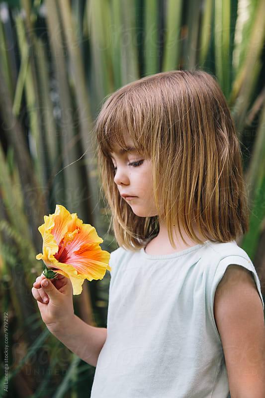 Child holding flower by Ali Lanenga for Stocksy United