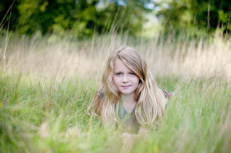 Girl laying in long grass by CHRISTINA K for Stocksy United