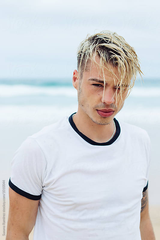 Handsome young man with wet hair on the beach by Susana Ramírez for Stocksy United