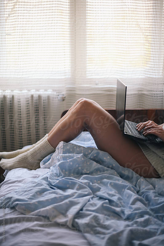 Woman using a laptop in her bed by Marija Mandic for Stocksy United
