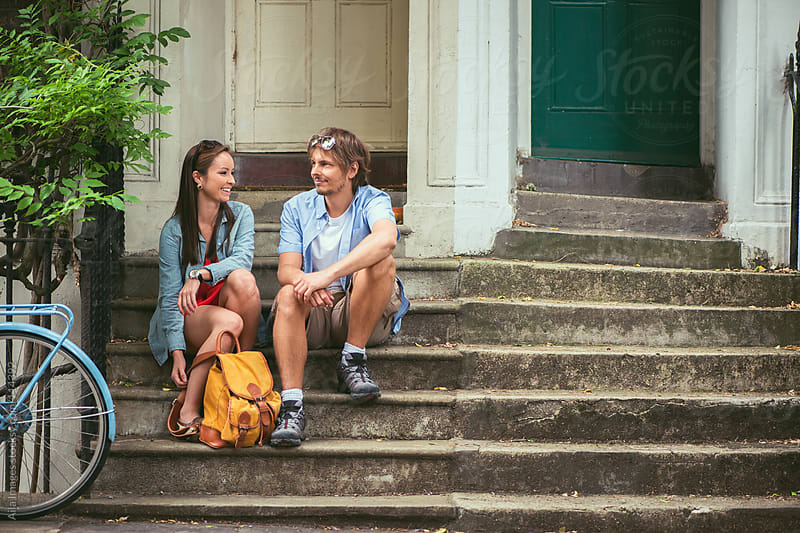 Couple waiting on the steps of their house by Aila Images for Stocksy United
