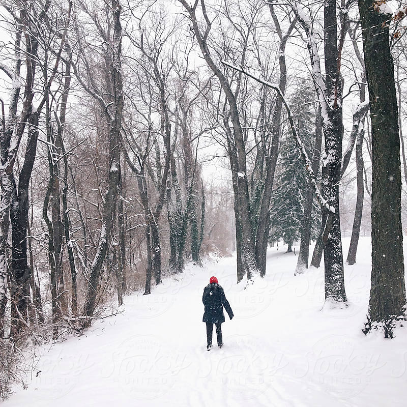 A woman wearing a red hat walks down a snowy lane. by Holly Clark for Stocksy United