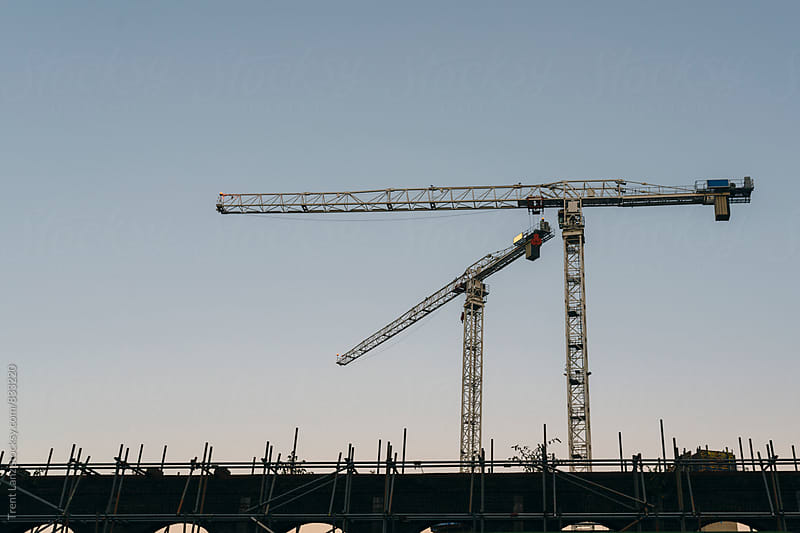 Architectural building site and two construction cranes from below by Trent Lanz for Stocksy United