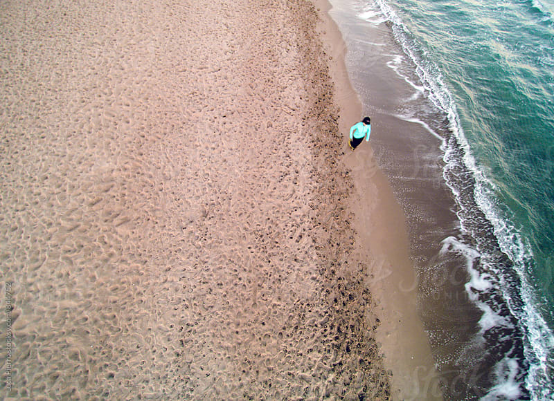 Aerial view of active woman walking on the beach by Luca Pierro for Stocksy United