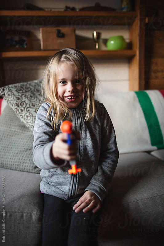 Little girl smiing and pointing toy gun by Rob and Julia Campbell for Stocksy United