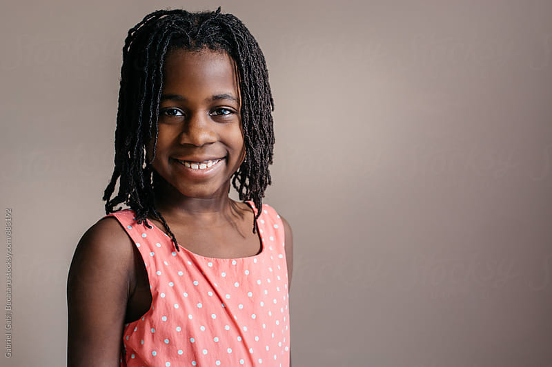 Smiling African American girl in rose dress by Gabriel (Gabi) Bucataru for Stocksy United