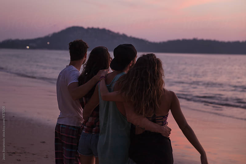 Group of friends watching sunset together on the beach by Jovo Jovanovic for Stocksy United