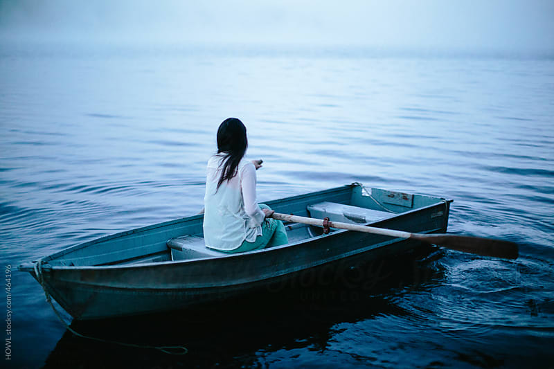 Mystical woman in row boat on a foggy New England morning  by HOWL for Stocksy United