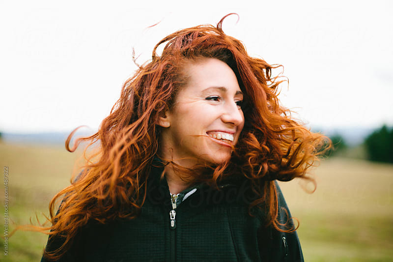 Smiling Woman with Red Curly Hair Being Blown in the Wind by Kristine Weilert for Stocksy United