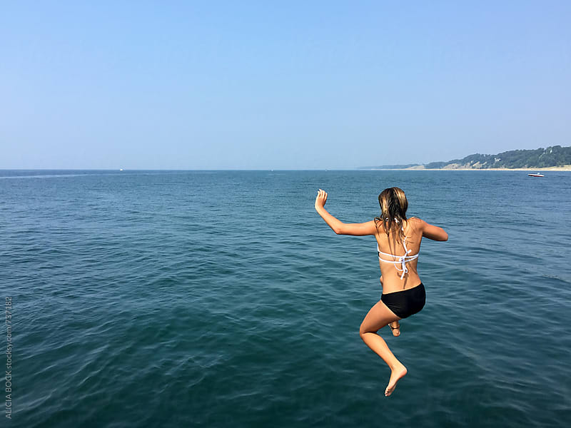 A Girl Jumping Into A Lake On A Clear Summer Day by ALICIA BOCK for Stocksy United