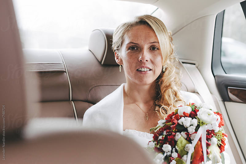 blonde freckled beautiful bride with bridal bouquet on the backseat of a car by Leander Nardin for Stocksy United