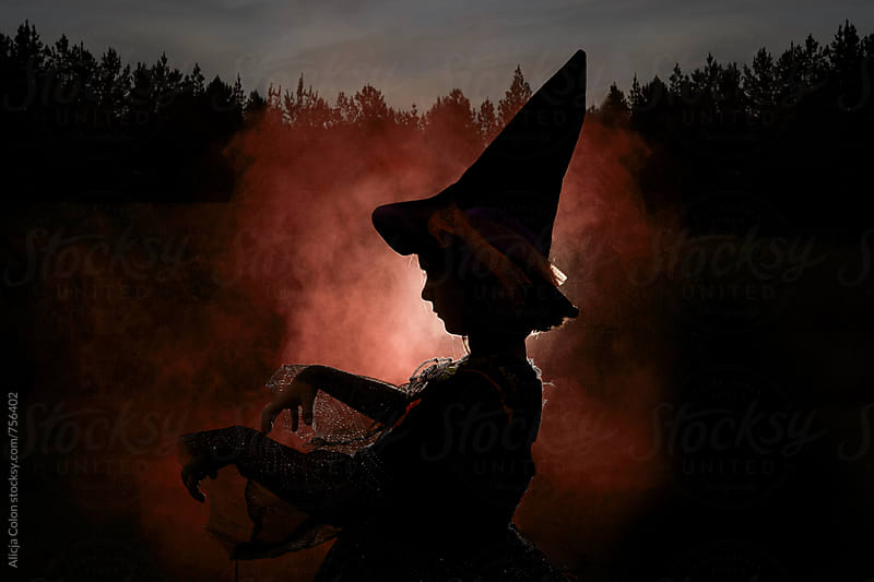 A silhouette of young girl in a witch costume by Alicja Colon for Stocksy United