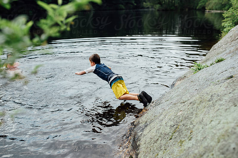 boy jumping in lake by Léa Jones for Stocksy United