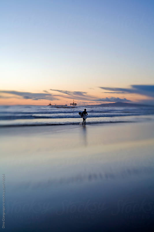 Silhouette of surfer holding surfboard during sunset by Dina Giangregorio for Stocksy United