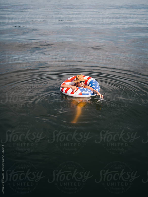 Young woman wearing hat floating on American flag tube in lake by Jeremy Pawlowski for Stocksy United