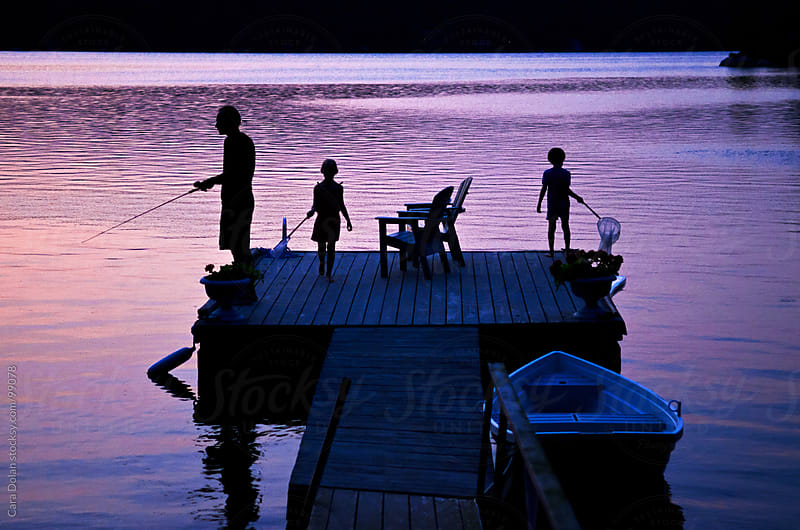 Family enjoying time together on the lake at sunset by Cara Dolan for Stocksy United