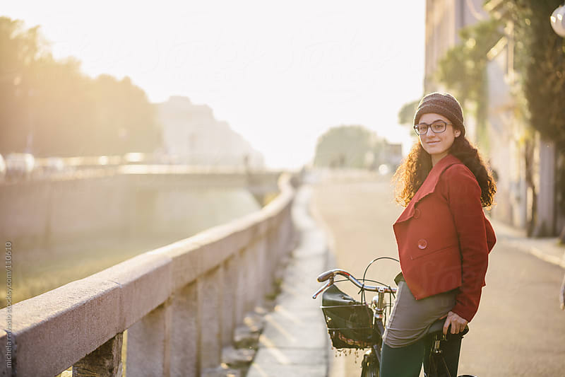Young woman with a bicycle along canals of Milan by michela ravasio for Stocksy United