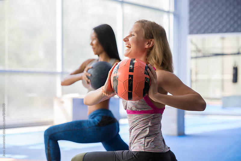 Two girls having fun working out with medicine balls by Jovo Jovanovic for Stocksy United