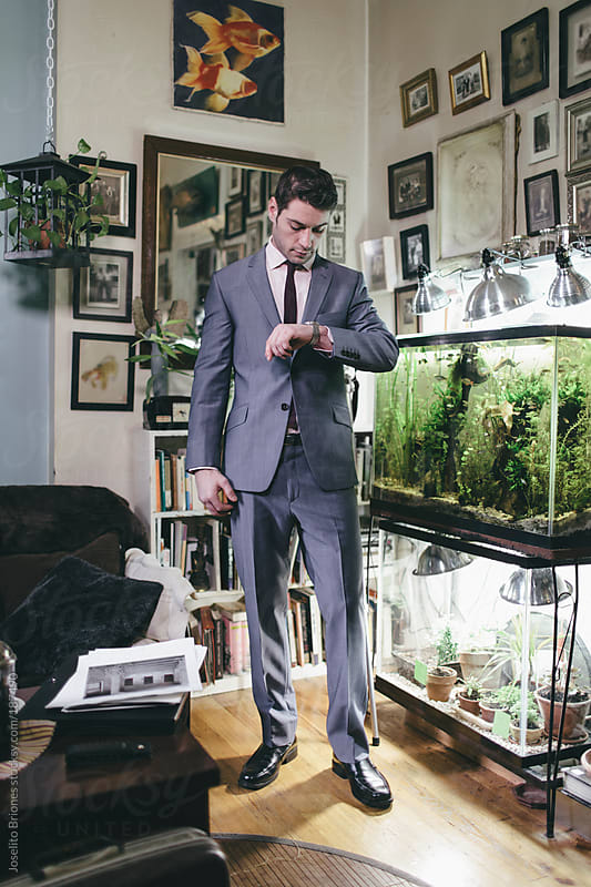 Portrait of a Man in Suit at Home in his Living Room next to Fish Tank by Joselito Briones for Stocksy United