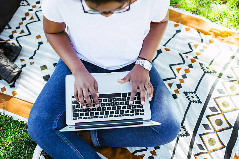 Latin woman using her laptop in the park from above. by BONNINSTUDIO for Stocksy United