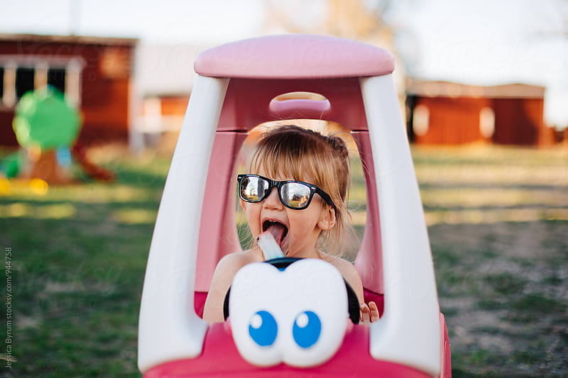 Small child eating popsicle in pink toy car by Jessica Byrum for Stocksy United