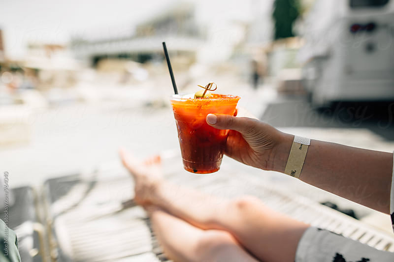 Young Woman Holding Cup Of Bloody Mary Cocktail At Hotel Swimming Pool by Luke Mattson for Stocksy United