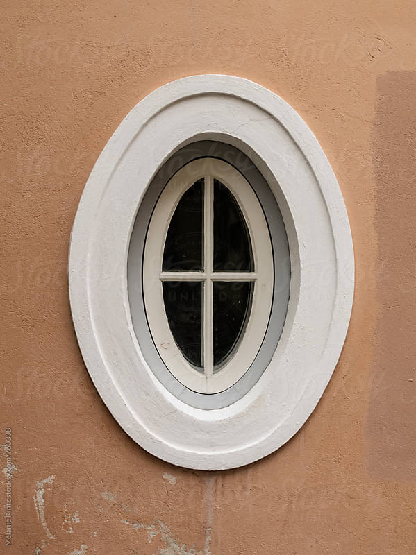 Oval window in brown wall by Melanie Kintz for Stocksy United