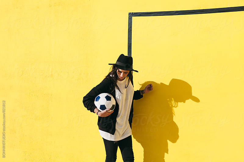Alternative woman holding a soccer ball in front of a yellow wall. by BONNINSTUDIO for Stocksy United