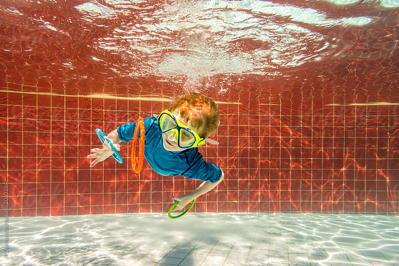 Little Boy Catching Rings Swimming Underwater In All Inclusive Resort Pool on Caribbean Vacation by JP Danko for Stocksy United